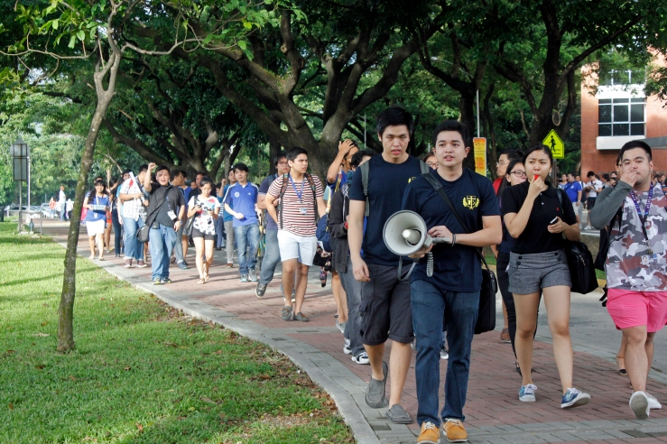 Student body representatives known as the Sanggunian ng mga Paaralang Loyola ng Ateneo de Manila (Student Body Council of Loyola Schools Students of the Ateneo de Manila University) lead rally participants to the gathering point a few meters outside campus gates.