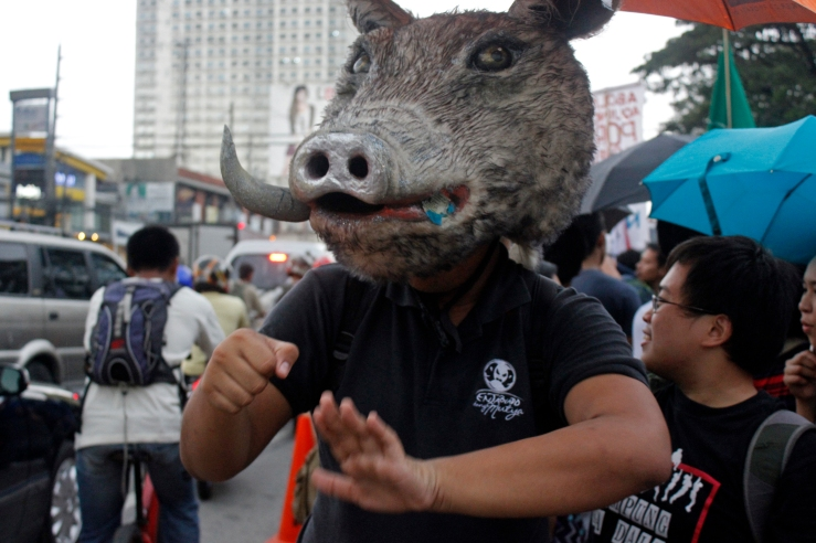 A student, wearing the head of a boar, signing passing motorists to honk their horns as a sign of support for the cause.